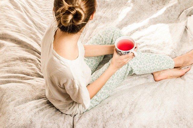 Žena v pyžame s čajom v ruke sediaca v posteli.jpg