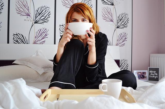 Žena v čiernej pyžame, ktorá pije z misky na posteli.jpg