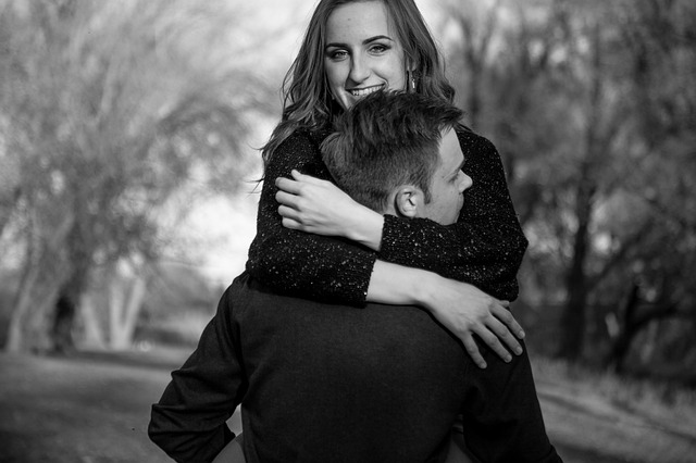 Mladá žena sa usmieva a objíma muža.jpg