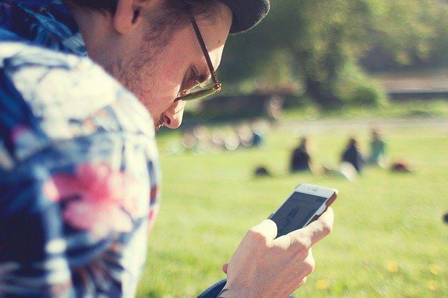 Muž sedí na lúke a pozerá do mobilného telefónu.jpg